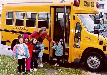 Teacher assisting students exiting from school bus