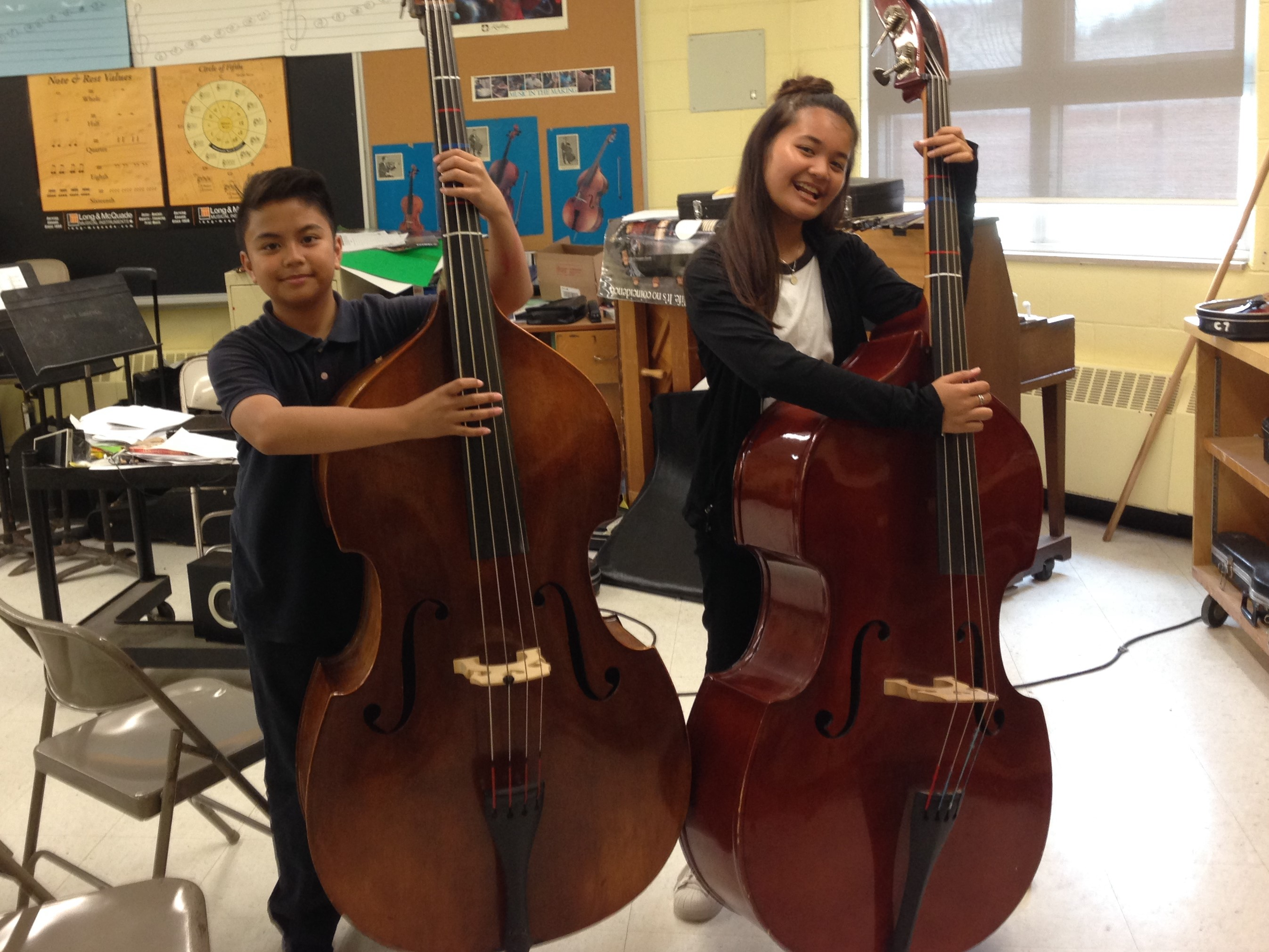 Two students holding accoustic basses